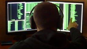 Le pirate informatique est regardé au code binaire Système de réseau pénétrant de pirate informatique criminel de sa pièce sombre banque de vidéos