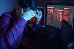 Le pirate informatique masculin anonyme couvre son visage de main tout en commettant un crime pour entailler le système sur le fo photographie stock libre de droits