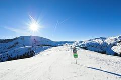 Le piste di corsa con gli sci su neve pende nel giorno soleggiato Fotografia Stock Libera da Diritti