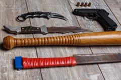 Le pistole dei banditi si trovano orizzontalmente in una fila su un pavimento di legno Vista ad angolo fotografia stock