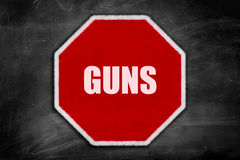 Le pistole scritte su una fermata firmano su una lavagna nera Immagini Stock