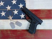 Le pistolet et l'identification étiquette avec les Etats-Unis les couleurs de drapeau que national peintes dessus se fanent Photo stock