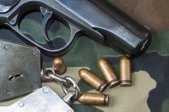 Le pistolet et la main d'arme à feu lancent des munitions sur le fond de camouflage de militaires Photo stock