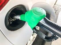 Le pistolet remplissant vert a collé dans le réservoir de gaz d'une voiture à une station service Le processus de remplir voiture photo stock