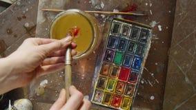 Le pitture dell'artista con le pitture dell'acquerello Pittura colorata miscele stock footage