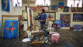 Le pitture dell'artista con pittura a olio Nello studio, fra i suoi propri impianti stock footage