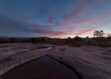Le pitture leggere di Predawn il cielo sopra pioggia hanno riempito gli stagni sulla MESA dell'uva spina nell'Utah del sud fotografia stock