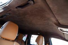 Le plafond de la voiture de SUV tirée par alkantara matériel doux brun dans l'atelier pour accorder et dénommer l'intérieur, vue  images libres de droits