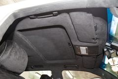 Le plafond de la voiture de SUV tirée par alkantara matériel doux noir dans l'atelier pour accorder et dénommer l'intérieur, vue  image stock