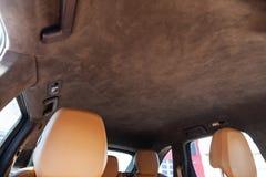 Le plafond de la voiture de SUV tir?e par alkantara mat?riel doux brun dans l'atelier pour accorder et d?nommer l'int?rieur, vue  images libres de droits