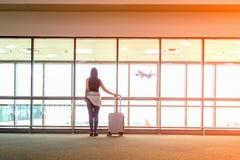 Le plan et le sac à dos de femme de voyageur voient l'avion au vitrail d'aéroport, le sac de touristes a de prise de fille Photographie stock libre de droits