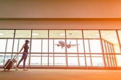Le plan et le sac à dos de femme de voyageur voient l'avion au vitrail d'aéroport, sac de touristes de prise de fille Photographie stock libre de droits