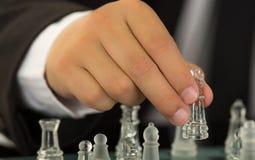 Le plan rapproché équipe des mains portant la pièce d'échecs en verre mobile de costume et de chemise blanche sur le panneau de j Photos libres de droits