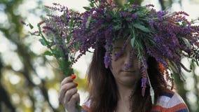 Le plan rapproché, belle fille avec une guirlande sur sa tête des fleurs de bleuet rassemble un bouquet des fleurs de champ à dis banque de vidéos