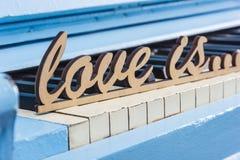 Le plan rapproché bleu de piano avec des clés noires et blanches avec amour des textes est Photos libres de droits