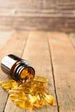 Le plan rapproché complète la bouteille de vitamines sur le fond en bois images libres de droits