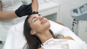 Le plan rapproché le cosmetologist de docteur dans une robe de chambre et des gants exécute des procédures de laser sur le visage clips vidéos