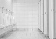 Le plan rapproché couvre de tuiles le mur dans la toilette de l'homme avec la vue de toilette par les urinoirs et la petite pièce Photos libres de droits