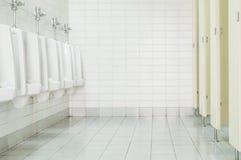 Le plan rapproché couvre de tuiles le mur dans la toilette de l'homme avec la vue de toilette par les urinoirs et la petite pièce Image stock