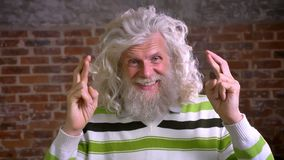 Le plan rapproché a croisé des doigts de grand-père caucasien avec de longs cheveux blancs et barbe bouclée se tenant droits et r clips vidéos