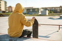 Le plan rapproché d'un adolescent s'est habillé dans un hoodie de jeans se reposant en parc de patin et tenant une planche à roul Images stock