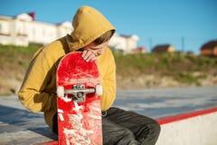 Le plan rapproché d'un adolescent s'est habillé dans un hoodie de jeans se reposant en parc de patin et tenant une planche à roul Image stock