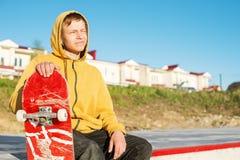 Le plan rapproché d'un adolescent s'est habillé dans un hoodie de jeans se reposant en parc de patin et tenant une planche à roul Photo stock