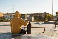 Le plan rapproché d'un adolescent s'est habillé dans un hoodie de jeans se reposant en parc de patin et tenant une planche à roul Images libres de droits