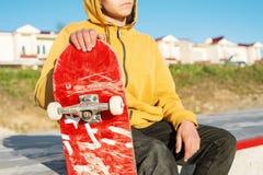 Le plan rapproché d'un adolescent s'est habillé dans un hoodie de jeans se reposant en parc de patin et tenant une planche à roul Photographie stock