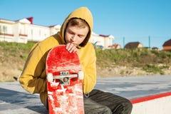 Le plan rapproché d'un adolescent s'est habillé dans un hoodie de jeans se reposant en parc de patin et tenant une planche à roul Photos libres de droits