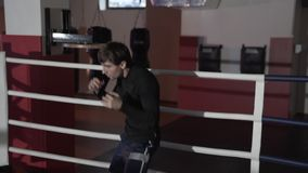Le plan rapproché d'un cadre cultivé d'un jeune homme dans les shorts et le Rashgarde de sports établit la technique des poinçons clips vidéos