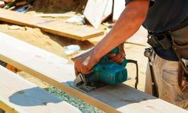 Le plan rapproché d'un charpentier employant une circulaire a vu pour couper un grand panneau de bois images libres de droits