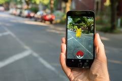 Le plan rapproché d'un homme jouant Pokemon disparaissent Photographie stock