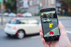 Le plan rapproché d'un homme jouant Pokemon disparaissent Photos libres de droits