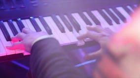 Le plan rapproché d'un homme joue le synthétiseur sur des clés banque de vidéos