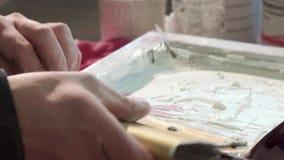 Le plan rapproché d'un homme d'un travailleur de typographie peignent de petits tableaux de bord banque de vidéos