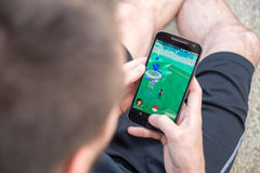 Le plan rapproché d'un jeune homme jouant Pokemon disparaissent Photographie stock libre de droits