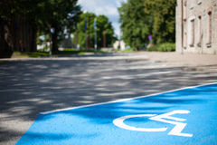 Le plan rapproché d'un parking réservé handicapé vide a peint le bleu avec un symbole blanc de fauteuil roulant sur l'asphalte no Photos libres de droits