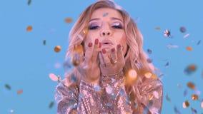 Le plan rapproché d'une belle blonde gonfle les confettis des ailerons qui se trouvent sur ses paumes Il regarde dans l'appareil- clips vidéos