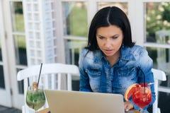 Le plan rapproché d'une belle femme étonnée a vu quelque chose dans son ordinateur portable et a été très étonné Jeunes regards e images libres de droits