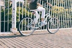 Le plan rapproché d'une femme dans une veste et les jeans montant une ville font du vélo Photographie stock libre de droits