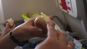 Le plan rapproché d'une femme répand le beurre sur le pain dans un avion clips vidéos