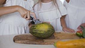 Le plan rapproché d'une femme remet couper le melon frais avec le couteau et le hachoir en bois dans la cuisine à la maison Coupu clips vidéos