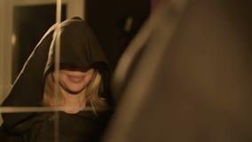 Le plan rapproché d'une magicienne de fille devant un miroir met dessus le capot de son costume à maintes reprises Appareil-photo clips vidéos