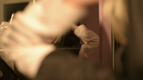 Le plan rapproché d'une magicienne de fille devant un miroir met dessus le capot de son costume à maintes reprises Appareil-photo banque de vidéos