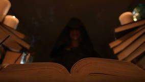Le plan rapproché d'une magicienne satisfaite de fille dans une chambre noire par lueur d'une bougie s'est créé un gâteau Tient u banque de vidéos