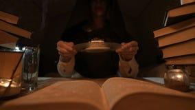Le plan rapproché d'une magicienne satisfaite de fille dans une chambre noire par lueur d'une bougie s'est créé un gâteau Tient u clips vidéos