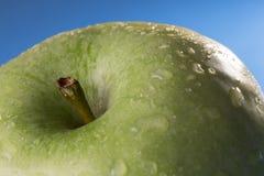Le plan rapproché d'une pomme verte avec de l'eau se laisse tomber photographie stock
