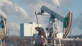Le plan rapproché d'une pompe fonctionnante pour l'extraction de pétrole brut et d'un ` s de centrale pétrochimique siffle des ém image libre de droits