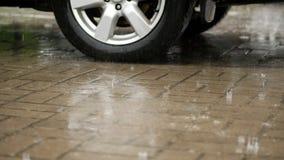 Le plan rapproché d'une roue de voiture, voitures sont mouillés dans le parking, de grandes baisses tombent avec éclabousse dans  banque de vidéos